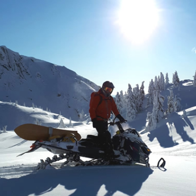 A man stands on a snowmobile with the sun hovering overhead.