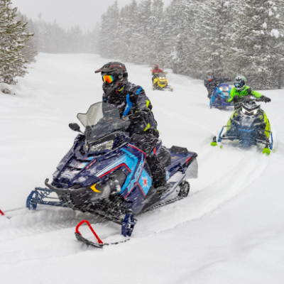 A line of snowmobiles ride through the snow.