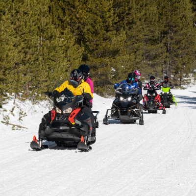 A row of four snowmobiles drive towards the camera.