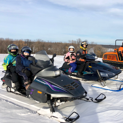 Five people ride three vintage snowmobiles in a Manitoba field.