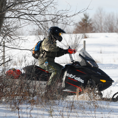 A man rides a snowmobile in the woods.