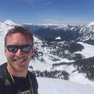 Josh Salzmann smiles in the foreground with snowy mountains in the background.