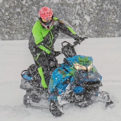 Kadie McCallum wears a pink helmet with a green and black coat and rides a blue and green snowmobile through a snowstorm.