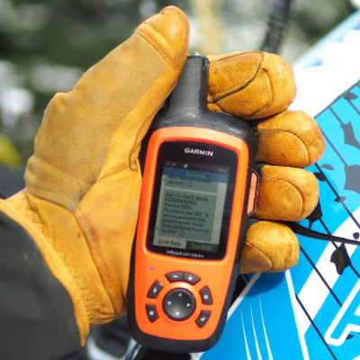 A yellow-gloved hand holds an orange Garmin inReach.