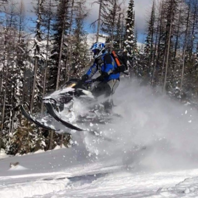A snowmobile gets big air, leaving a powder trail in its wake.