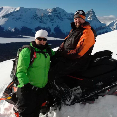 Les and Amanda L'Heureux pose on their snowmobiles in Kakwa Provincial Park.