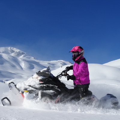 A pink snowmobiler rides a black snowmobile through rolling hills of white snow.