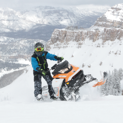 A man stands next to his snowmobile on a mountain.