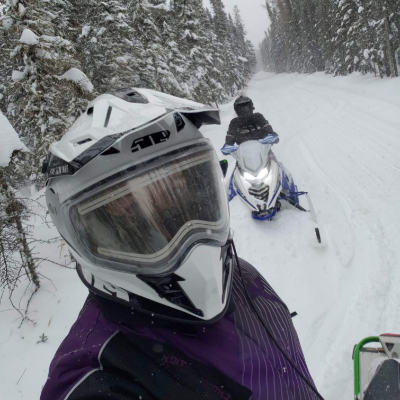 A snowmobiler looks into the camera from close range on a trail among trees.
