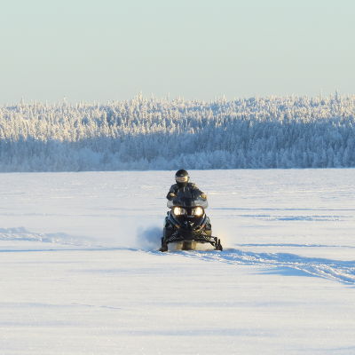 A sledder rides through a field with mountains in the background
