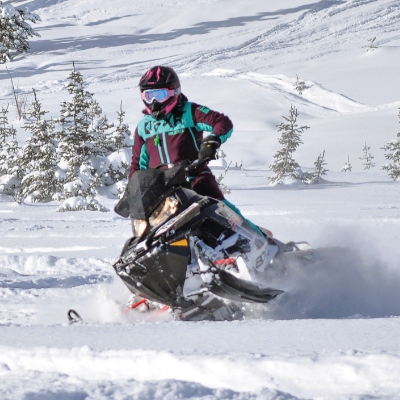 A woman rides a snowmobile through the woods.