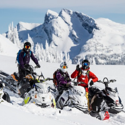 Three snowmobilers pose in the mountains in Revelstoke.