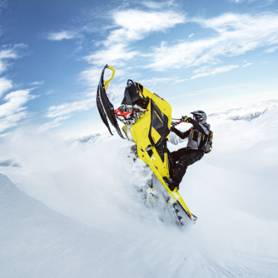 A snowmobiler climbs a mountain on a yellow Ski-Doo Summit 850 E-TEC.