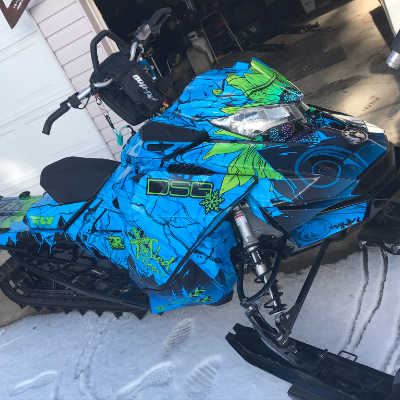 A blue and green sled wrap on a snowmobile.