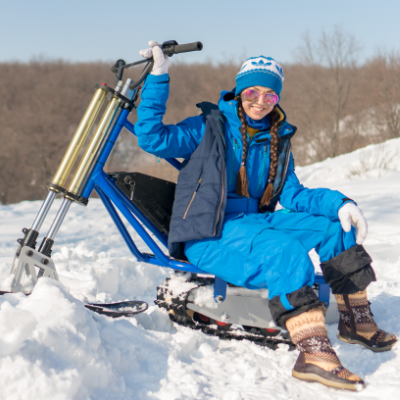 A woman sits on an electric snow scooter.