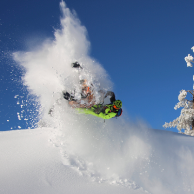 A green snowmobiler gets air off of a jump at the top of a mountain next to a snow covered tree.