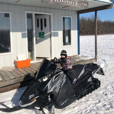 A small child sits on a full-sized black snowmobile.