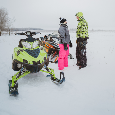 A couple stand next to their snowmobiles and visit.