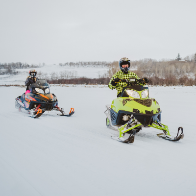 Two snowmobilers race across a trail.
