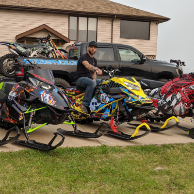 Chris Thiessen stands next to a pickup with a custom-wrapped dirt bike in the back.