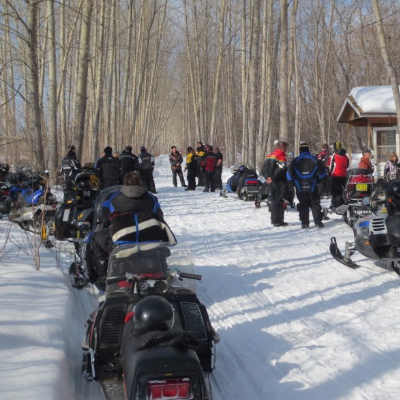 A row of snowmobiles are gathered to take while riders socialize in the background