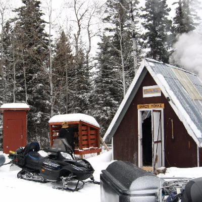 A warm-up shelter is pictured with snowmobiles parked in front of it.