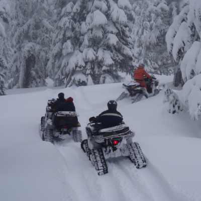 Three ATV riders with tracks ride through the snow