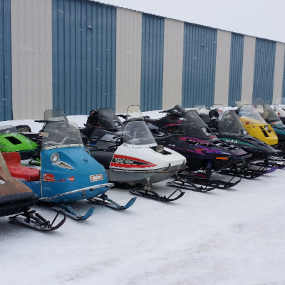 A row of vintage snowmobiles is parked beside a building