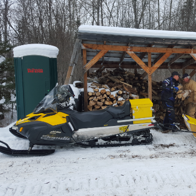 Volunteers with the Lee River Snow Riders load up and supply wood for five warm-up shelters.