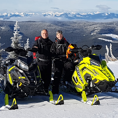 A couple posing by their Polaris snowmobiles on Connell Ridge.