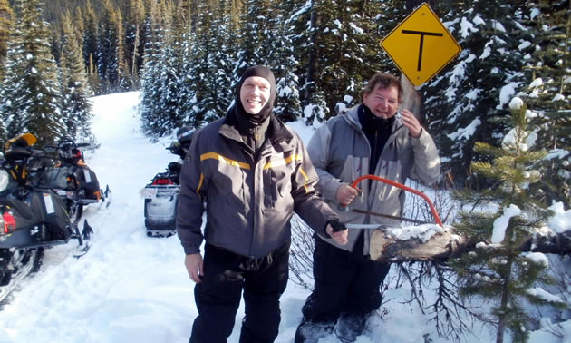 Two snowmobilers clearing a tree off the trail.