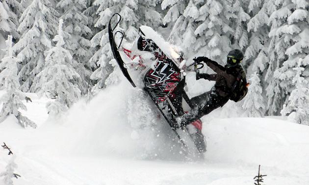 Snowmobiler popping a wheelie on a sled.