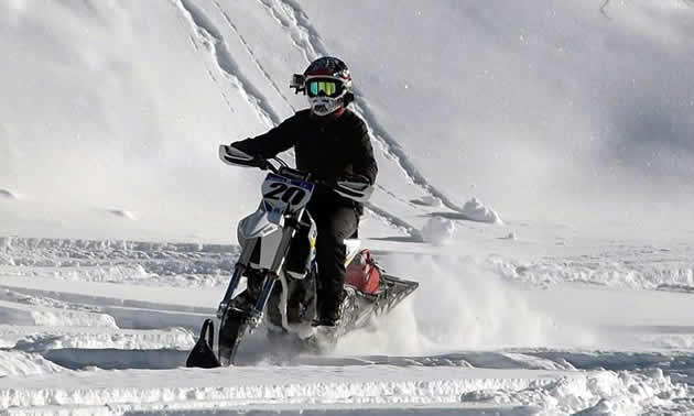 A woman riding a Timbersled snow bike.