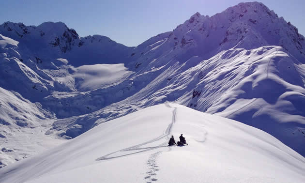 Two snowmobilers sitting on top of a ridge in Valdez, Alaska.