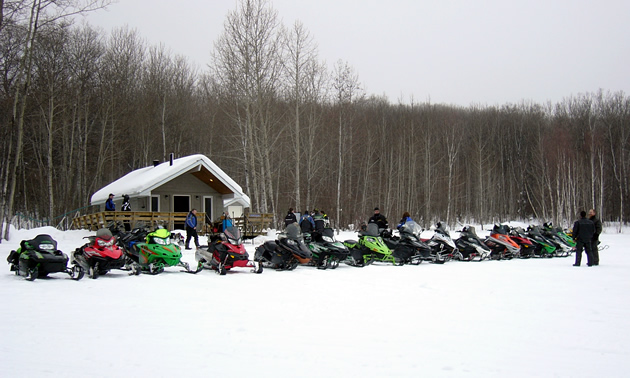 A group of sledders lined up in front of a shelter.