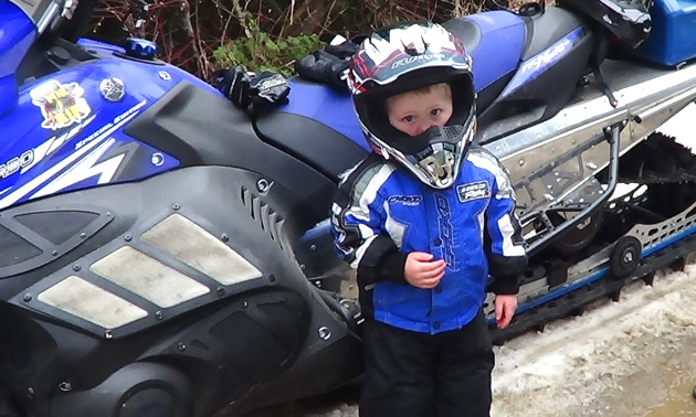 A young boy in a snowmobile suit.
