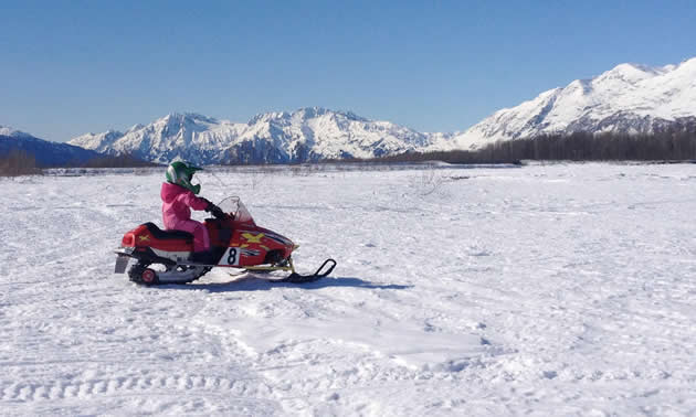 A kid riding a youth-sized snowmobile in Valdez.