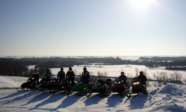 A group of sledders lined up on top of an overlook.