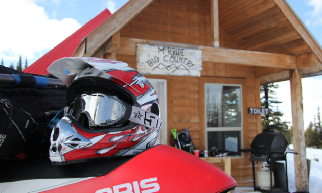 A snowmobiler's helmet is set upon the back of a snowmobile in the foreground. A wooden cabin with BBQ is in the background.
