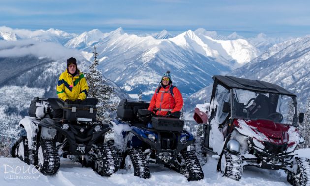 An elderly couple sit on their ATVs with tracks on top of a snowy mountain.