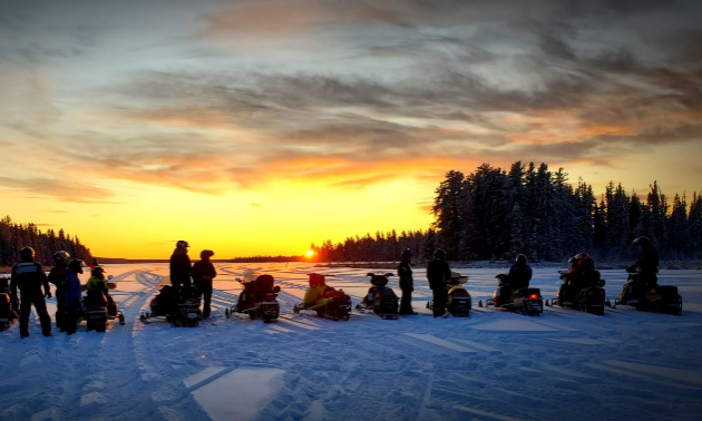 A row of snowmobilers watch the sunset like an orange ball of fire in the distance.