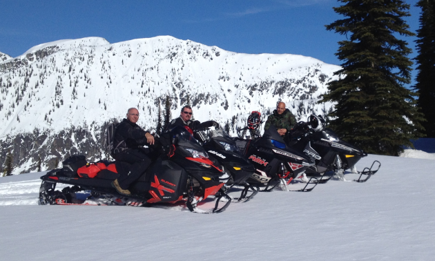 A row of snowmobilers smile on their sleds with a mountain in the background.