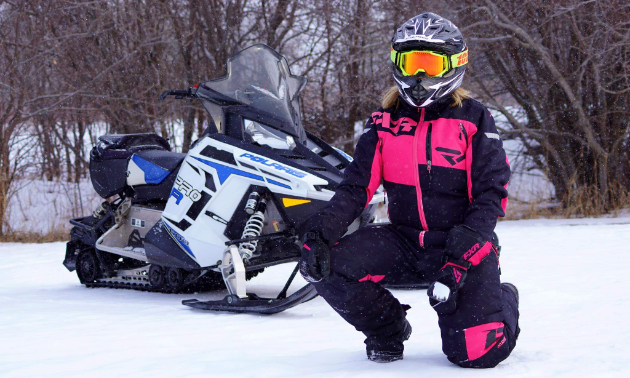A woman wearing pink and black clothes kneels in front of a white and black and blue snowmobile in Gimli, Manitoba.