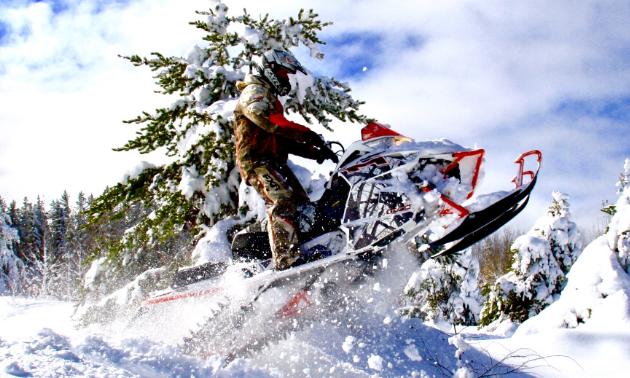 A snowmobiler plows through a snowy jump in Flin Flon, Manitoba.