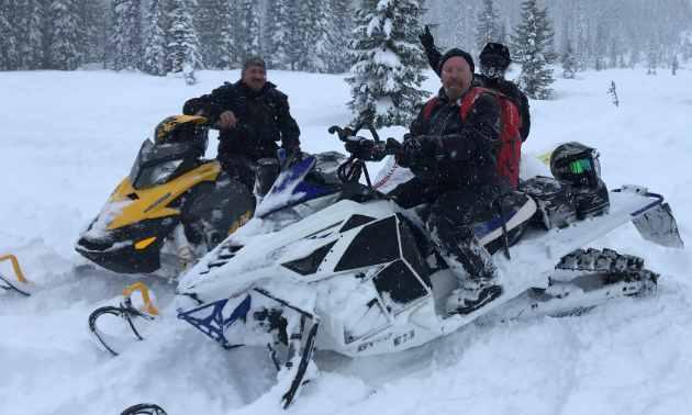 Three snowmobilers smile for the photo.