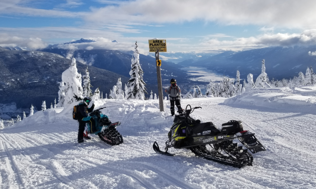 A couple riders stand next to snowmobiles at a summit in Revelstoke.