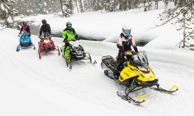 Snowmobilers ride down a snowy trail.