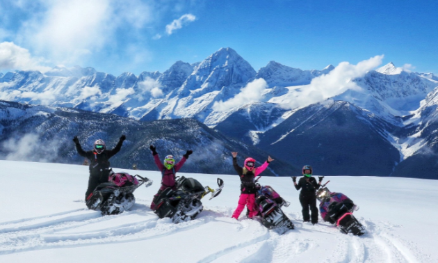 Four women hold their arms up as they stand next to their snowmobiles in front of the Rocky Mountains.
