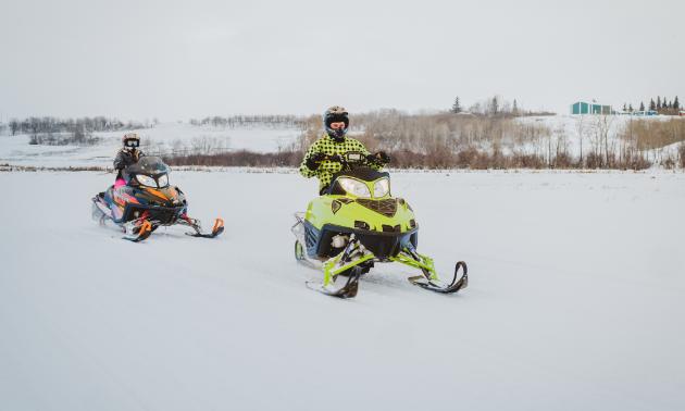 Two snowmobilers race across a trail.