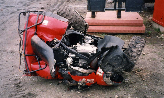 A red ATV lies in a crumpled heap next to a railway track.